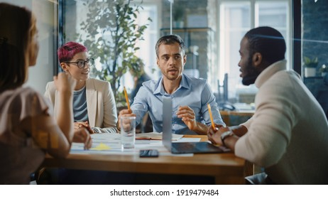 Office Meeting in Conference Room: Handsome Specialist Talks about Firm Strategy with Diverse Team of Professional Businesspeople. Ambitious, Creative Start-up Team Discuss Data, Design, Planning