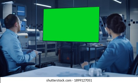 Office Meeting: Confident Female Engineer Talks to Project Manager, Watching Interactive Digital Whiteboard TV that Shows Green Screen Chroma Key Display. Modern Factory with Machinery