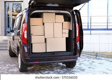 Office moving concept. Cartoon boxes in a car trunk