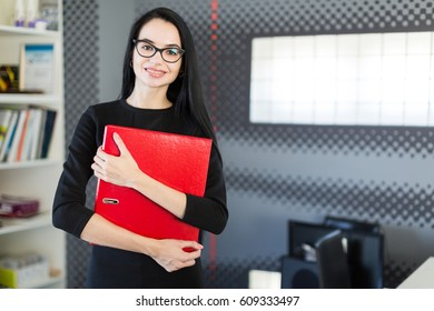 Office on background, beautiful young brunette caucasian businesswoman in black dress and glasses hold red paper folder, hugs folder