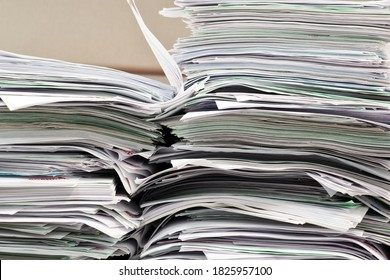 Office paperwork stacked haphazardly on a desk, closeup image. Overworked concept in business environment.