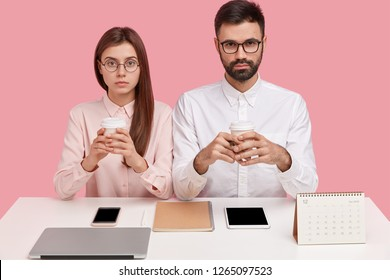 Office perfectionists sit at desktop hold mobile phones, have serious expressions, dressed in elegant shirt, have proper order of things on desk, use wireless internet, aim to everything perfect