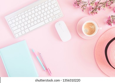 Office pink table, notepad, keyboard, flowers, coffee, hat, notebook, stationery on pink background. Business minimal concept for women. Flat lay, top view, copy space