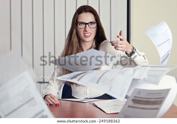 office portrait of beautiful dissatisfied business woman angrily throwing documents to the camera