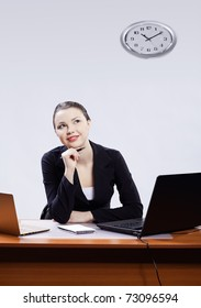 office portrait of beautiful happy thoughtful business woman sitting at her workplace with two laptops on gray