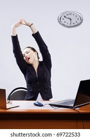 office portrait of beautiful tired business woman stretching and yawning at her workplace with two laptops on gray