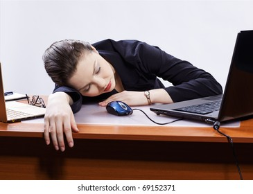 office portrait of beautiful young business woman sleeping at her workplace between two laptops on gray