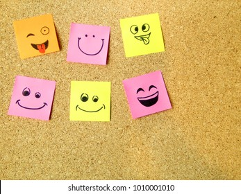 office post it notes with various smiley happy faces on cardboard with copy space
