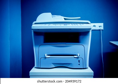 Office printer multi-functional device on table plugged in a communication port on a wall