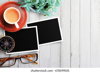 Office or relax workplace - two blank photo frames,flower and glasses with cup of coffee on old wooden table or office wooden desk background with copy space. top view(Space and composition for use)