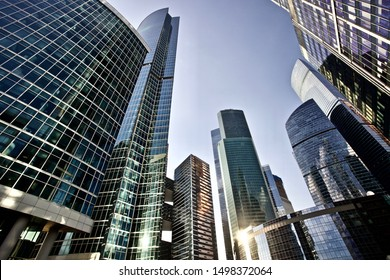 Office and residential skyscrapers on bright sun and clear blue sunset sky background. Commercial real estate. Modern business city district. Office buildings exterior. Financial city district.