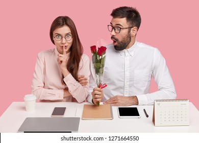 Office romance, dating and secrecy concept. Speechless young girl makes hush gesture while recieves nice bouquet from colleague, asks not tell to anybody about their secret love at workplace.