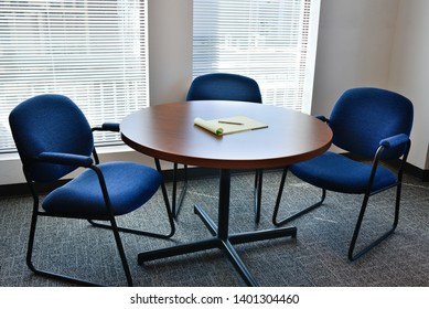 Office with round table three empty blue chairs waiting for meeting no people.  Windows with blinds in background. Neat, clean and tidy interior.  Pad of paper and single pen on table