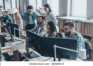 Office routine. Group of young business people in smart casual wear working and communicating while sitting at desk in the office