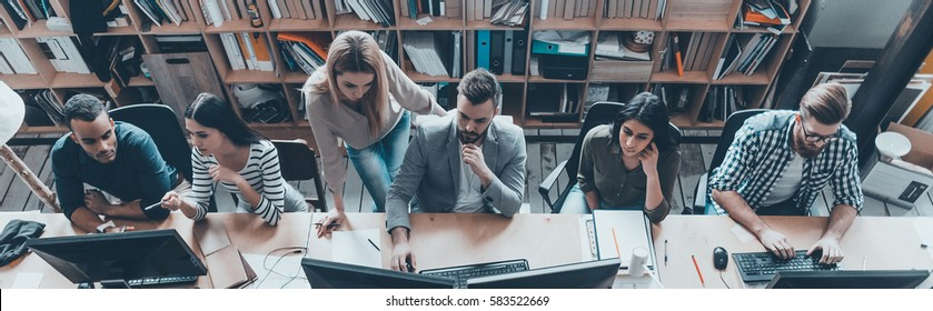 Office routine. Top view of group of young business people in smart casual wear working together while sitting at the large office desk