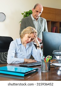 Office scene with angry chief and careless aged female secretary