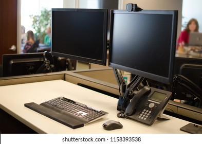 Office setting - Dual monitor computer and phone on desk with working adults out of focus in background