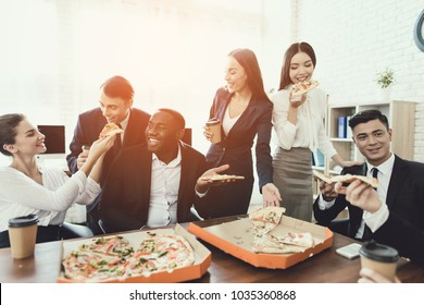 The office staff eat pizza and drink coffee in the business office. They have a break in their work. They are resting.