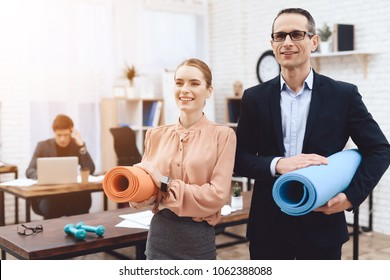 Office staff hold gymnastic mats. They work in a business office. They are preparing to rest.