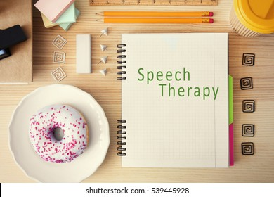 Office stationery on wooden table. Text SPEECH THERAPY on notebook page