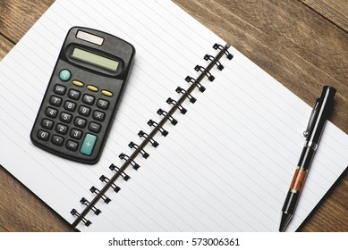 Office still-life with pen and calculator on brown wooden table.