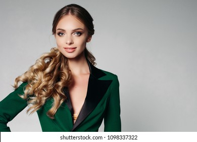 Office strict style. Blond girl with beautiful wavy hair in a green, stylish office jacket. Friendly, smiling with restraint. Looks at the camera Isolate on a gray background