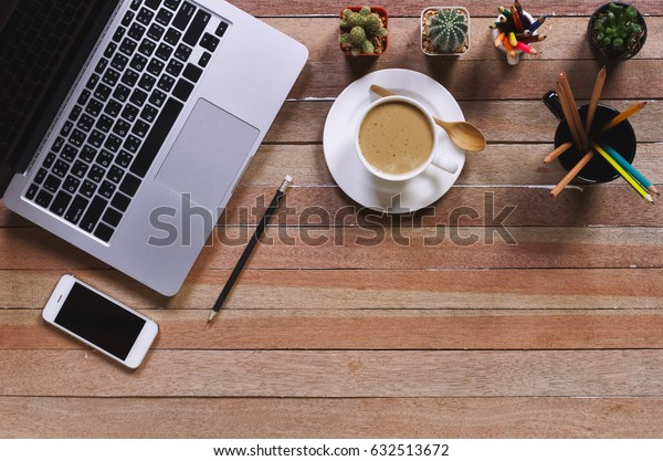 Office stuff and it gadgets display on top view business desk with copy space at text of picture. Creative table, modern project. Business mockup at empty laptop smartphone device on wood background.