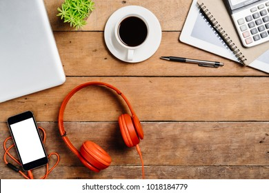 Office stuff with laptop,blank screen smart phone,headphone,notebook,tablet,calculator and cup of coffee.Top view with copy space.Working desk table concept.