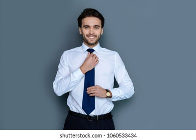 Office style. Handsome delighted positive man looking at you and fixing his tie while getting ready to work