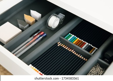 Office supplies in desktop drawer. Writing pens, pencils, paper clips, color sheets for notes. Workplace order. Work at home.