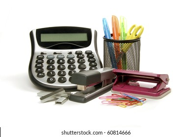 Office supplies including a calculator, punch, stapler, paperclips and scissors