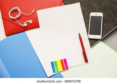 office supplies on a desk. Top view, Blank sheet of paper and accessories, Still life with folders, mobile phone, glasses, watch, pencil. contents of a business workspace organized and composed