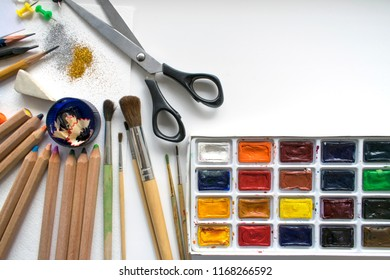 Office supplies on a white sheet of paper. Back to school and supplies on white background. Multicolored pencils,  watercolors, scissors and glitter. stationery for the schoolboy, studen. mockup