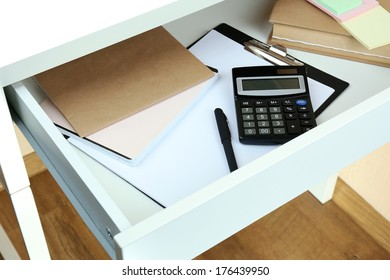 Office supplies in open desk drawer close up