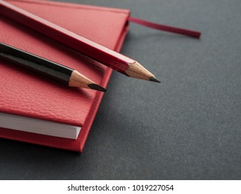 Office supplies: a red notepad and pencils on a black background. Top view. Copy space.