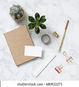 Office supplies in rose gold color with houseplants.