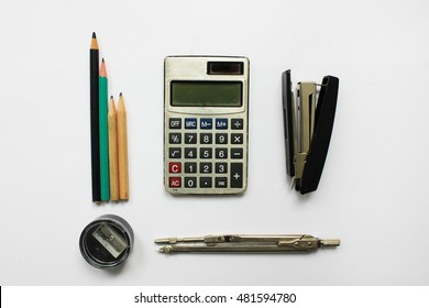 Office supplies and studying tools calculator, stapler, pencil sharpener, pencils and divider isolated on white table background with empty copyspace. Study, work, counting and calculation concept
