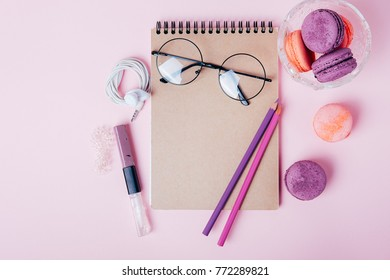 Office supplies for young woman. Flatlay with blanknote, glasses, pencils and cookies.