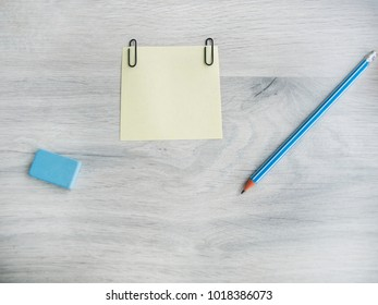 Office table with accessories: blank sheet, eraser, pencil on a wooden gray table. Viewing from above and copying text.