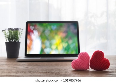 Office table with Beautiful couple knitted fabric heart shape, heart shape bokeh background on laptop screen and violet flower pot. view from front office table. valentine's day concept.