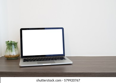 office table with blank screen laptop and garden plant garden on cement wall background, view from front office table, concept of business lifestyle.