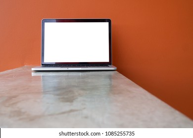 Office table with Blank screen for text laptop, notebook on orange color cement wall texture background. view from front laptop.