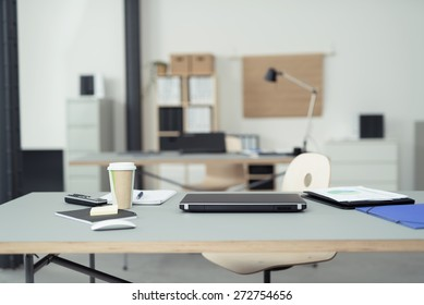 Office Table of a Businessman with Office Supplies, Laptop Computer, Mobile Phone and a Cup of Coffee on Top.