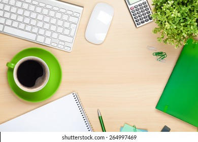 Office table with coffee cup, computer and flower. View from above with copy space