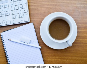 Office table with cup of coffee,computer and notepad