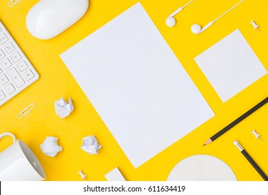Office table desk with blank paper sheet, calculator, paper ball, pencil, earphone, computer mouse and office accessories on colorful background. business and office supplies flat lay concept.