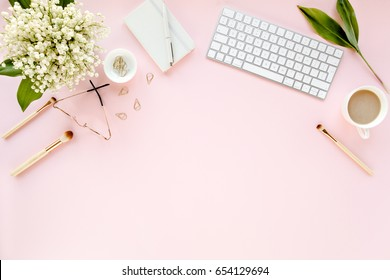 Office table desk with computer, bouquet lilies, clipboard. magazines, social media. Top view. Flat lay. Home office workspace. Women's fashion accessories isolated on pink background.