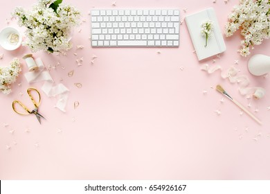 Office table desk with computer, bouquet lilac, clipboard. magazines, social media. Top view. Flat lay. Home office workspace. Women's fashion accessories isolated on pink background.