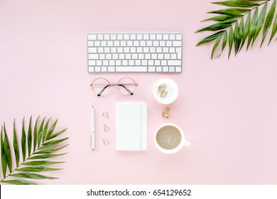 Office table desk with computer,  green leaves palm, clipboard. Magazines, social media. Top view. Flat lay. Home office workspace. Women's fashion accessories isolated on pink background.