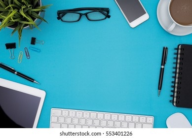 Office table desk with computer, tablet, pen, coffee cup, flower, eye glasses, supplies and white blank note pad on blue background, Top view and copy space for text